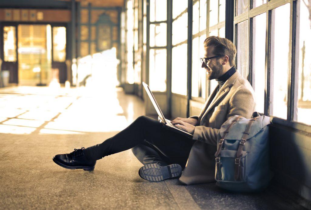 homem sentado no chão feliz com a tradução do seu documento