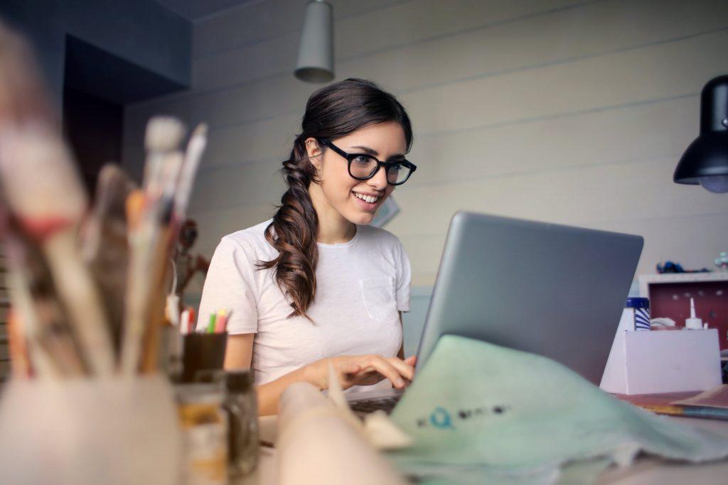 mulher feliz na frente do laptop esperando a tradução