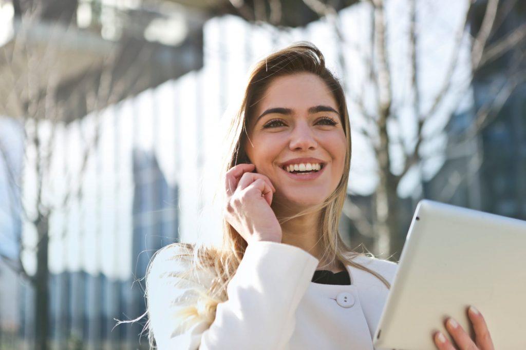 mulher sorrindo pedindo um orçamento de tradução no celular
